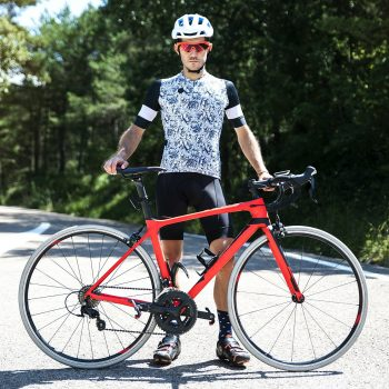 Portrait of young cyclist with his bike on the road.